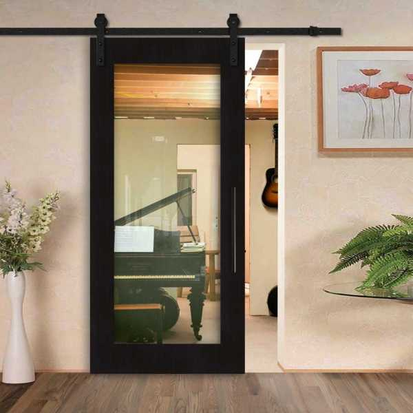 Sliding veneered barn door with clear glass insert and carbon steel sliding system